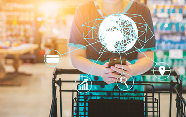 girl leaning on shopping cart, using a mobile phone, trolley in department store bokeh with online shopping and payment icon customer network connection on screen, m-banking for marketing technology