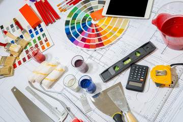 Professional decorator using a digital tablet, work tools.