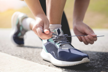 Cropped shot of young women runner tightening running shoe laces.