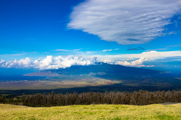 Grand view of the island of Maui in Hawaii, with Maalaea Bay on the left and Kalului Bay on the right and the volcano Mauna Kahalawai of the West Maui Mountains in the center, with spectacular clouds