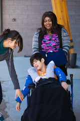 Two caregivers taking care of disabled boy in wheelchair outdoors