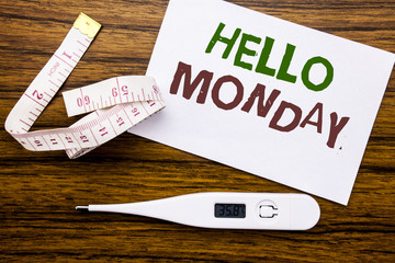 Conceptual hand writing text caption showing Hello Monday. Business concept for Day Week Start written on sticky note paper on wood background. Meter and thermometer for fitness subject.