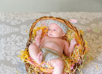 newborn baby with bunny ear hat laying in Easter basket