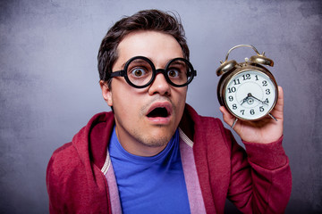 Young man in eyeglasses with metal alarm clock