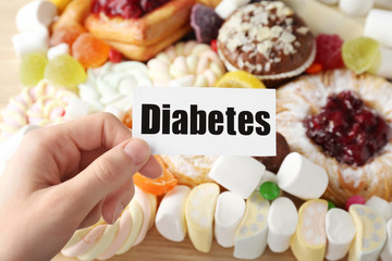 Woman holding card with word DIABETES over sweets, closeup