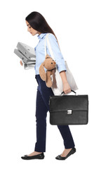 Young businesswoman with briefcase, bunny toy and folders walking on white background