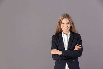 Beautiful fashionable woman in elegant suit on grey background
