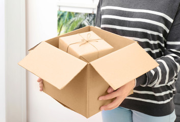 Woman holding parcel with gift box at home