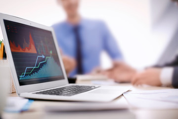 Laptop with stock data on table in office. Financial trading concept