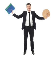 Businessman with notebooks and paint palette on white background