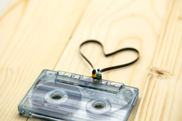 Miniature people : Couple of love sitting on Audio cassette with magnetic tape in shape of heart on wood background.