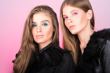 Fashion portrait of two beautiful young women in black. Bright professional makeup