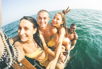 Young multiethnic friends taking selfie after swimming on sailing boat sea trip - Rich happy guys and girls having fun in summer party day - Exclusive vacation concept - Bright warm  vintage filter