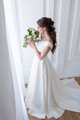 elegant bride in traditional white dress sniffing wedding bouquet