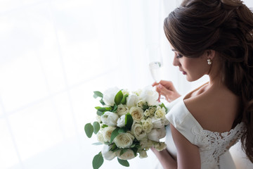 attractive bride in traditional dress with wedding bouquet and glass of champagne standing at window