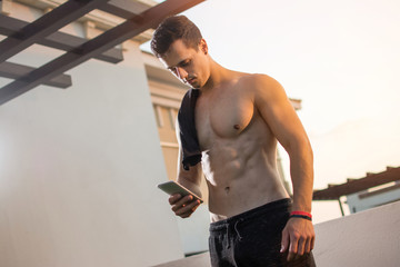 Handsome muscular man with shirt over shoulders text messaging on mobile phone outdoors.