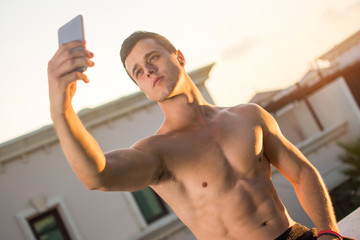 Handsome shirtless muscular man taking selfie while sitting on rooftop's wall outdoors during sunset.