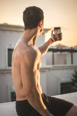 Rear view of young muscular man holding phone and taking selfie photo outdoors during sunset.