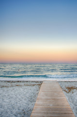 Scenic pastel color seaside sunset at a sandy beach of the mediterranian sea  with a wooden bridge,path leading to the ocean in painting style