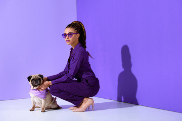 attractive african american young woman posing in purple suit with pug, ultra violet trend