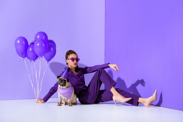 elegant african american girl posing with purple balloons and pug, ultra violet trend