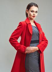 Business woman chief studio portrait in red coat.