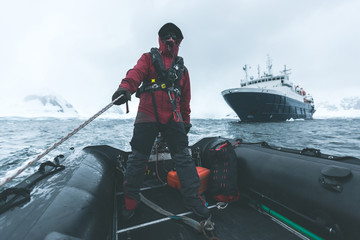 Man steering a Rubber Dinghy - Antarctica