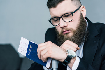 portrait of thoughtful businessman with passport and ticket in hand