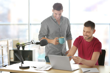 Young men with laptop indoors