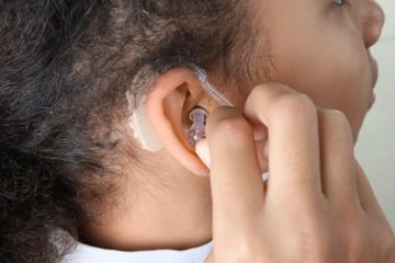 Little girl putting hearing aid in ear, closeup