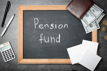 "Chalkboard with words ""Pension fund"", money and calculator on grey background"