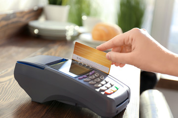 Woman using bank terminal for credit card payment in cafe