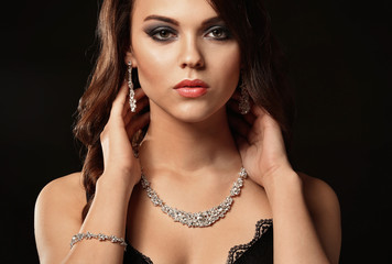 Beautiful young woman with elegant jewelry on dark background