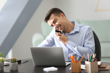 Young man talking on phone while working with laptop in office