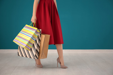 Beautiful young woman with shopping bags against color wall