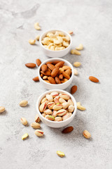 Fresh organic nuts, almonds, cashew, pistachio in a bowls on a light background.