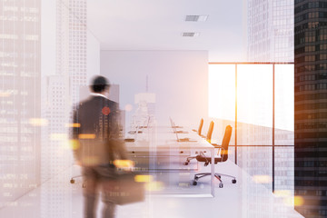 Businessman entering a white wall meeting room