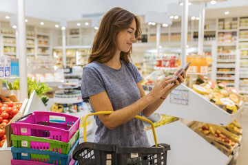 A pretty young female, using her mobile phone in modern market. Front of display fruits