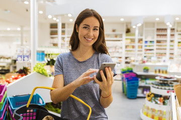Casual young female, using her cellphone in modern supermarket. Looking at camera