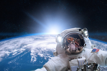 Astronaut in outer space on background of the Earth. Elements of this image furnished by NASA.