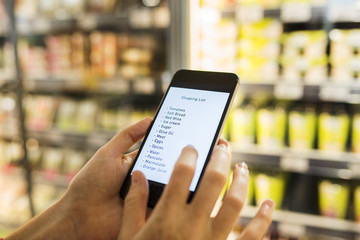 Female using cell phone while shopping in supermarket. Shopping list. Close-up hand