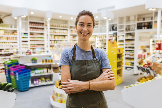 Happy natural young saleswoman in modern supermarket. Cross arms. Looking camera