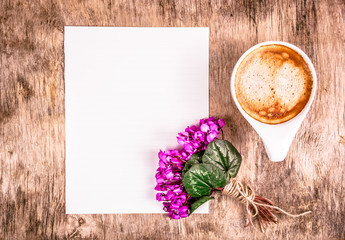 Cup of coffee and flowers. Empty sheet of paper and  cup of coffee on the table.