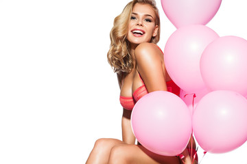 Beautiful smiling blonde in pink underwear sits on a white background with an armful of pink balls in a festive cheerful mood.