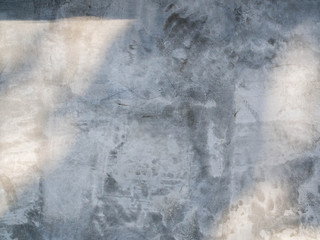 Closeup of concrete wall texture with the light and shadow cast on the surface.