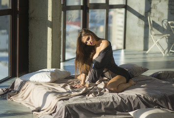 Young woman stretching in her bed after wake up in the bedroom