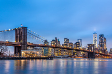Fototapete - Brooklyn bridge and New York City Manhattan downtown skyline at dusk with skyscrapers illuminated over East River panorama.