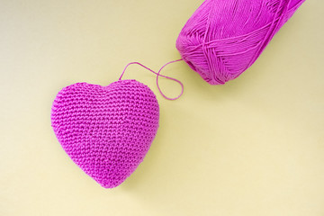Pink heart crocheted by hand. Made with a thread. The thread is not cut and attached to the heart.