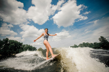 brunette woman in black swimsuit wakeboarding down the river