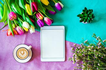 Freifläche auf Tablet Bildschirm mit buntem Hintergrund und Tulpen im Frühling von oben zu Ostern